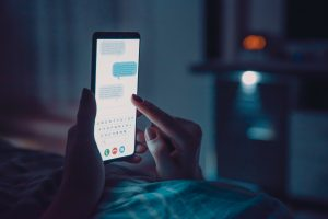 a person using their phone at night while in bed