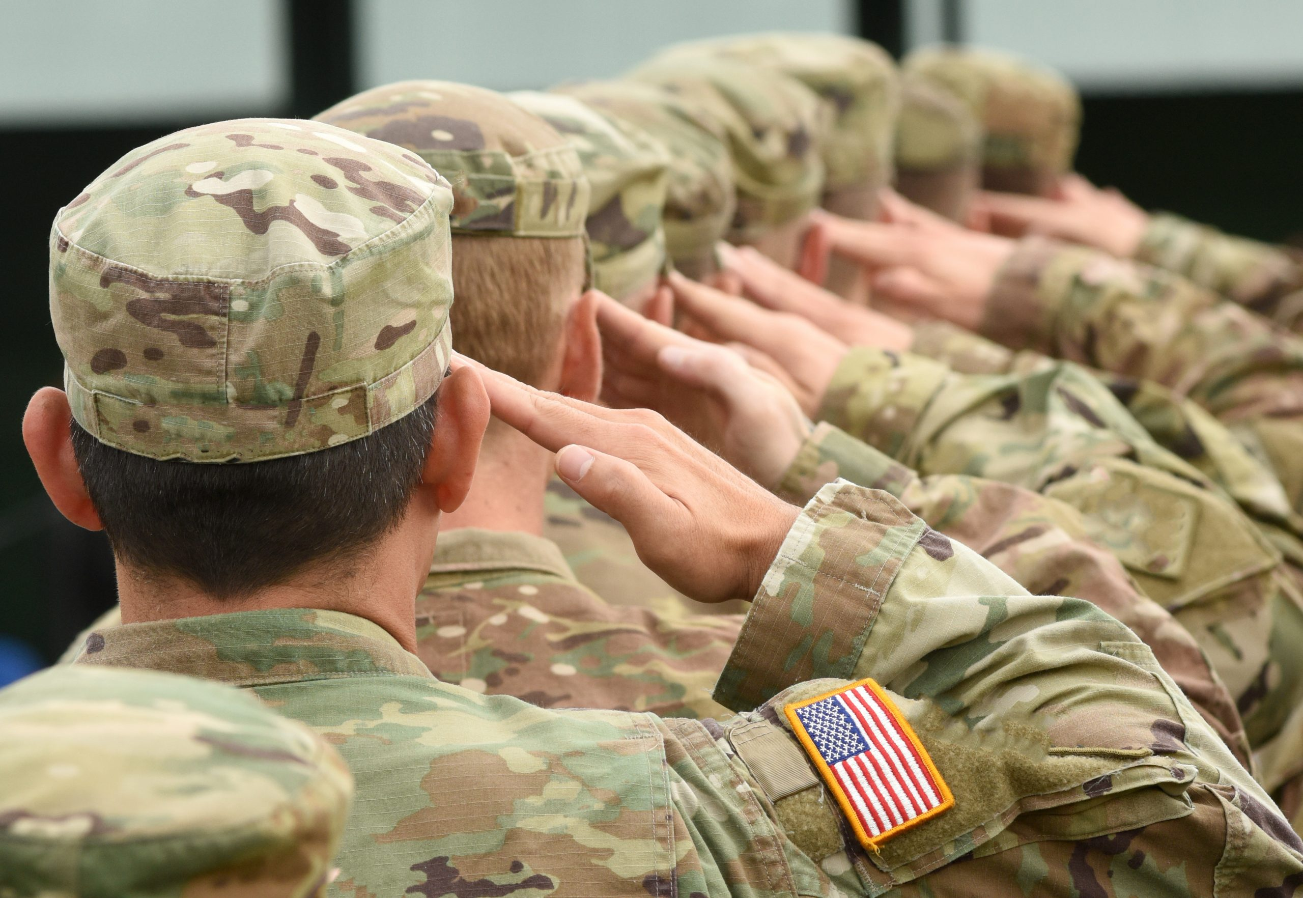 a line of military service members saluting
