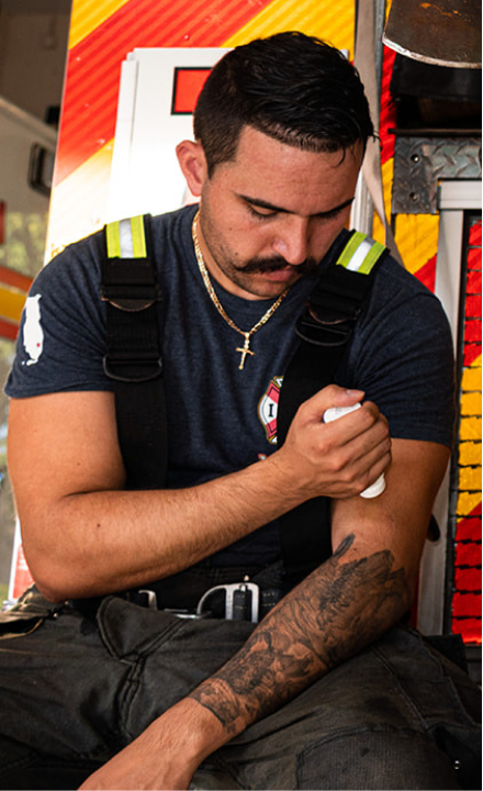 a firefighter sitting on the back of a fire truck using topical CBD for first responders