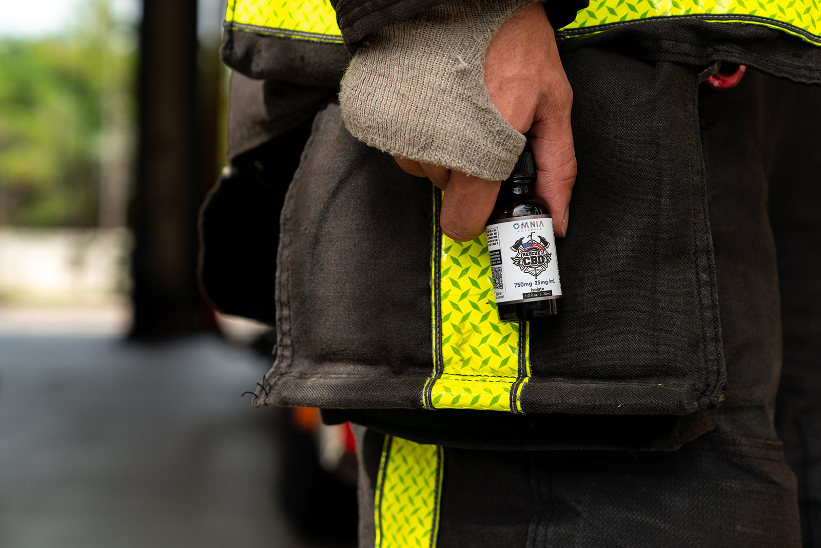 a firefighter wearing gear holding a bottle of rescue 1 CBD at his side
