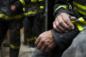 a firefighter seated after an incident with two other firefighters in the background